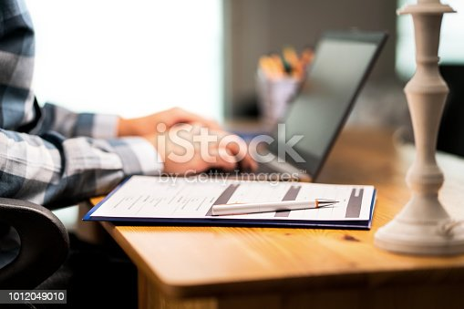 Survey form, customer satisfaction feedback poll, resume for job application or for college. Man writing with laptop.  Home or car insurance contract. Paper sheet and pen on desk.