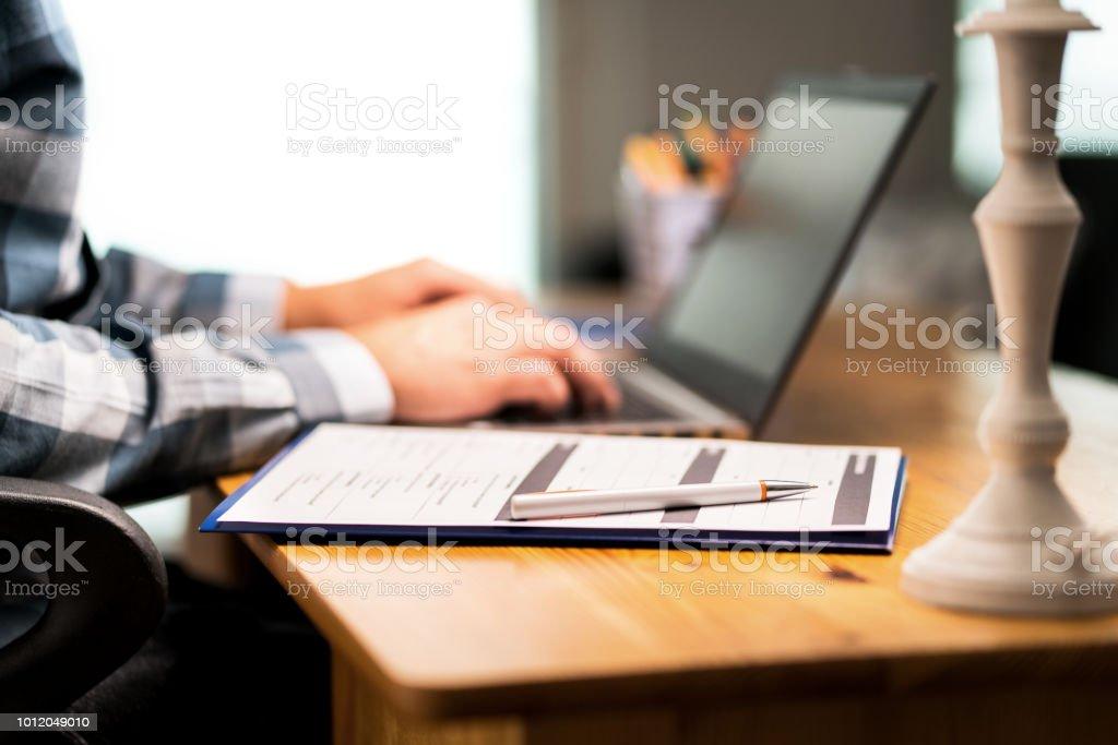Encuesta formulario de encuesta de retroalimentación de satisfacción al cliente, reanudar para solicitud de empleo o para la Universidad. Hombre escribiendo con el ordenador portátil.  Contrato de seguro de hogar o automóvil. Hoja de papel y lápiz. - foto de stock