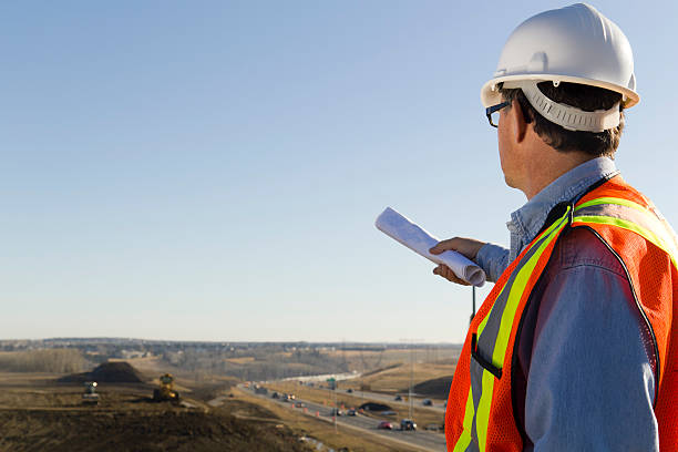 """Survey """"A royalty free image from the construction industry of an architect as he surveys a construction site, plans in hand."""" civil servant stock pictures, royalty-free photos & images"""