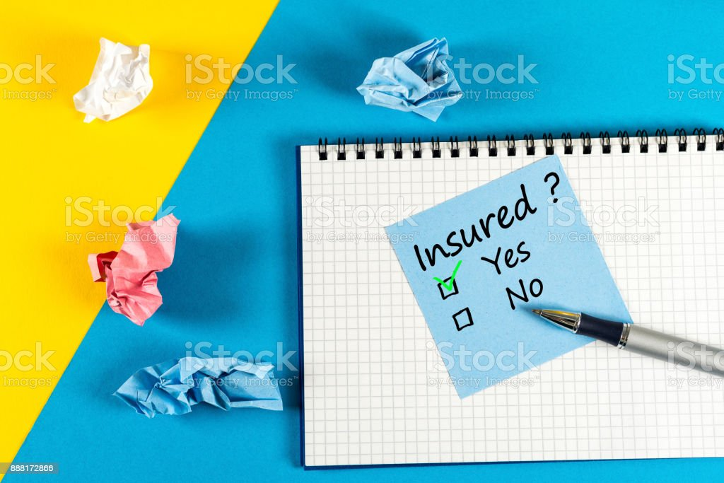 Survey with question Insured, Yes or no. Message at notepad at yellow and blue table, insurance agent stock photo