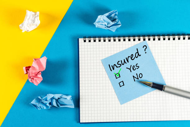 Survey with question Insured, Yes or no. Message at notepad at yellow and blue table, insurance agent Survey with question Insured, Yes or no. Message at notepad at yellow and blue table, insurance agent. general military rank stock pictures, royalty-free photos & images