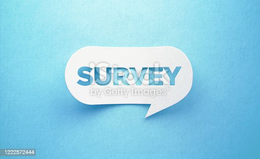 Survey written white chat bubble on blue background. Horizontal composition with copy space. Survey concept.