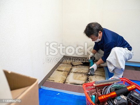 Japanese construction worker cutting the floor with power saw.