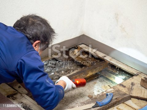 Japanese construction worker checking the underfloor space.