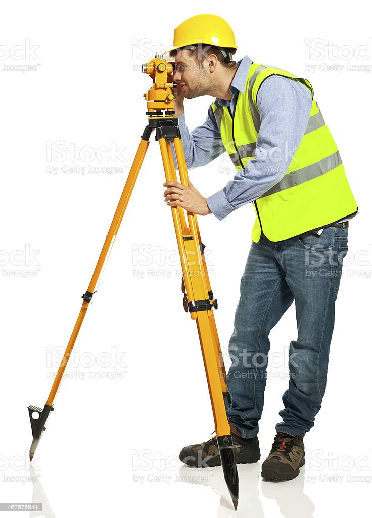 Surveyor Apprentice Full lenght portrait of young surveyor apprentice wearing hardhat and reflective vest, looking thought theodolite against white background. Studio shot. 20-29 Years Stock Photo