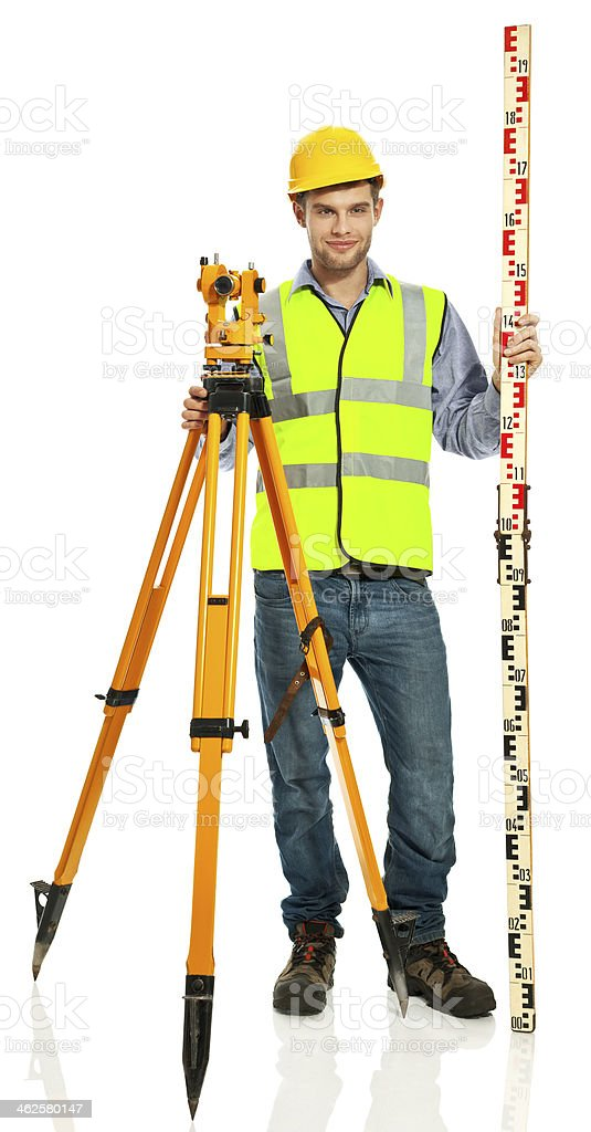 Surveyor Apprentice Portrait of smiling young surveyor apprentice wearing hardhat and reflective vest, standing with level rot and theodolite against white background. Studio shot. 20-29 Years Stock Photo