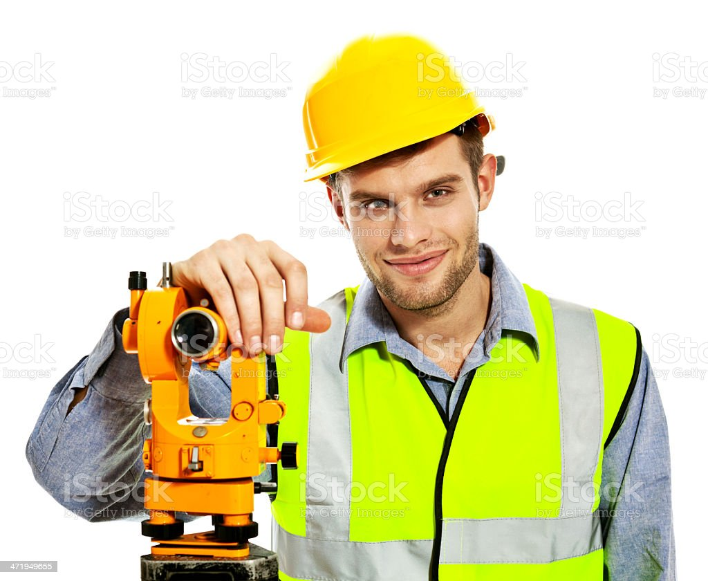 Surveyor Apprentice Portrait of smiling young surveyor apprentice wearing hardhat and reflective vest, standing with theodolite against white background. Studio shot. 20-29 Years Stock Photo