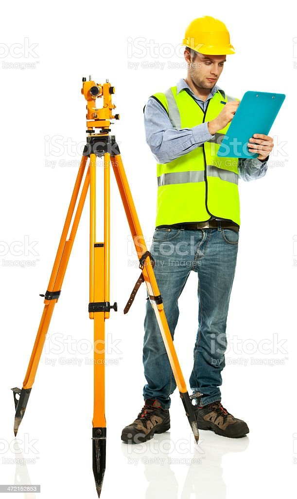 Surveyor Apprentice Young surveyor apprentice wearing hardhat and reflective vest standing next to theodolite and recording measurements.  Studio shot, white background. 20-29 Years Stock Photo