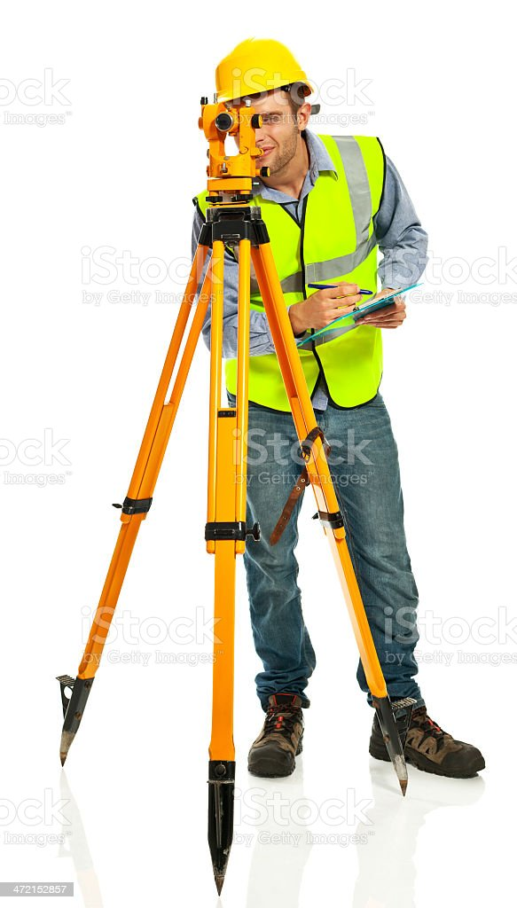 Surveyor Apprentice Young surveyor apprentice wearing hardhat and reflective vest looking through the theodolite and recording measurements.  Studio shot, white background. 20-29 Years Stock Photo