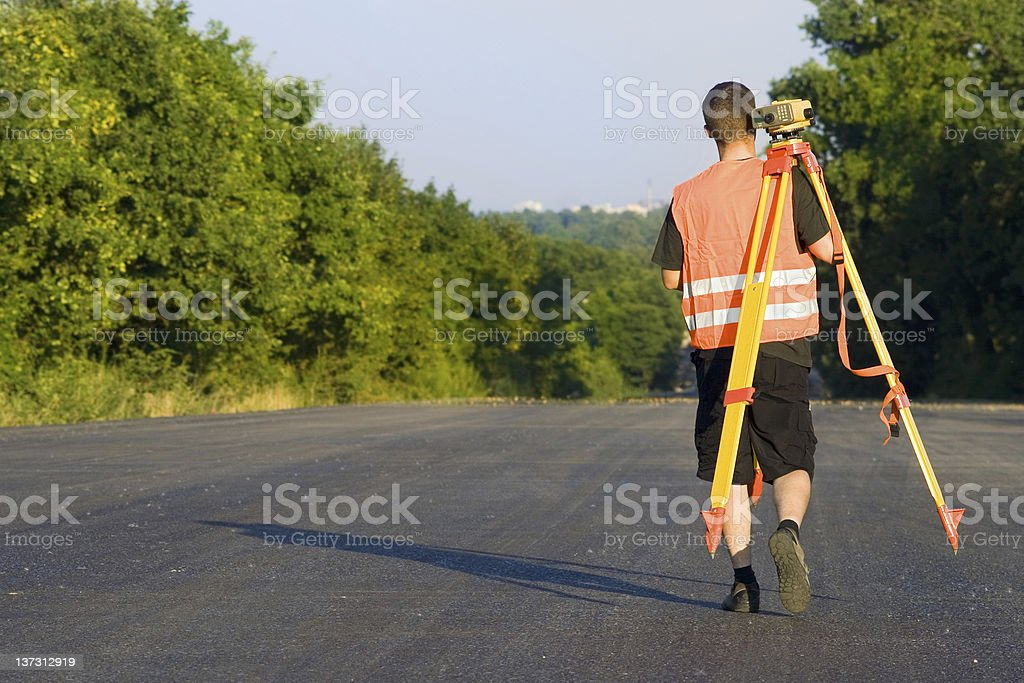 Surveyor changing the digital level position royalty-free stock photo