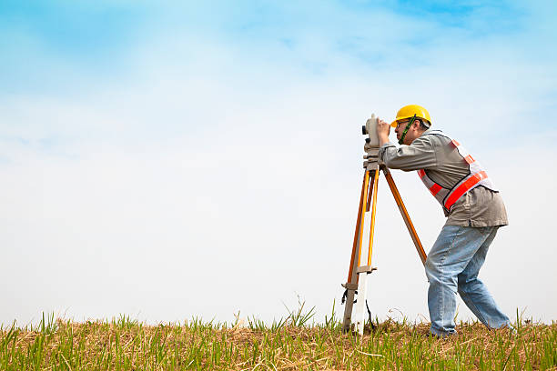 surveyor engineer making measure on the field - topography stock photos and pictures