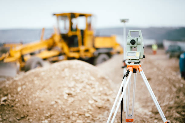 surveyor equipment gps system or theodolite outdoors at highway construction site. surveyor engineering with total station - perito foto e immagini stock