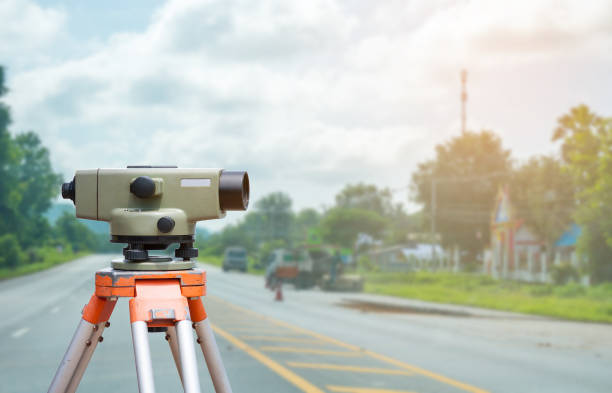 Surveyor equipment tacheometer or theodolite with road construction site background stock photo