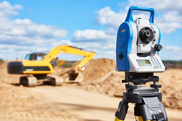 surveyor equipment theodolie at construction site with excavator stock photo