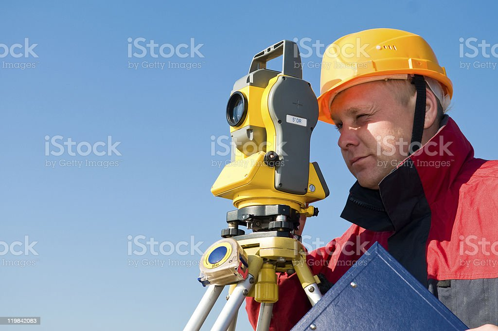 Surveyor looking at the thedolite stock photo