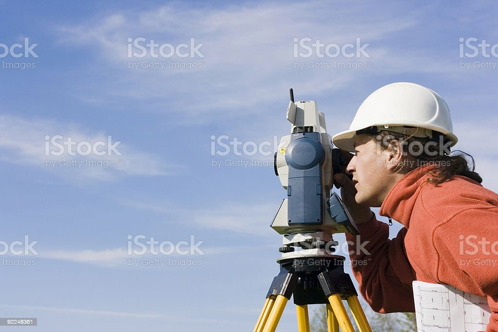 Surveyor measuring with a theodolite royalty-free stock photo
