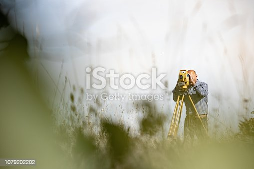 Surveyor Using Theodolite to Measure Land.