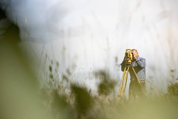 surveyor using theodolite to measure land - perito foto e immagini stock
