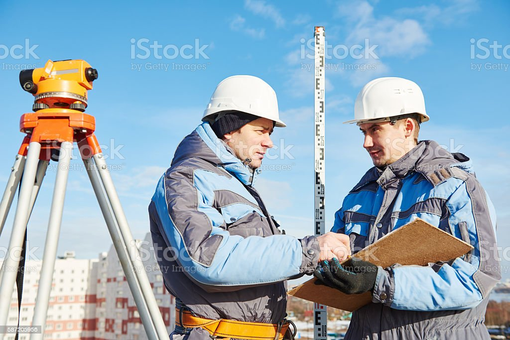 Surveyor workers with level at construction site stock photo
