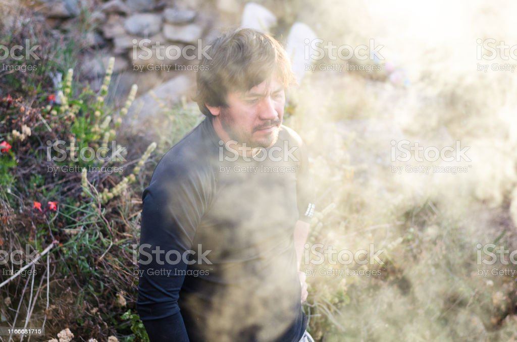 Survival Man is making bonfires in the winter forest, high on the...
