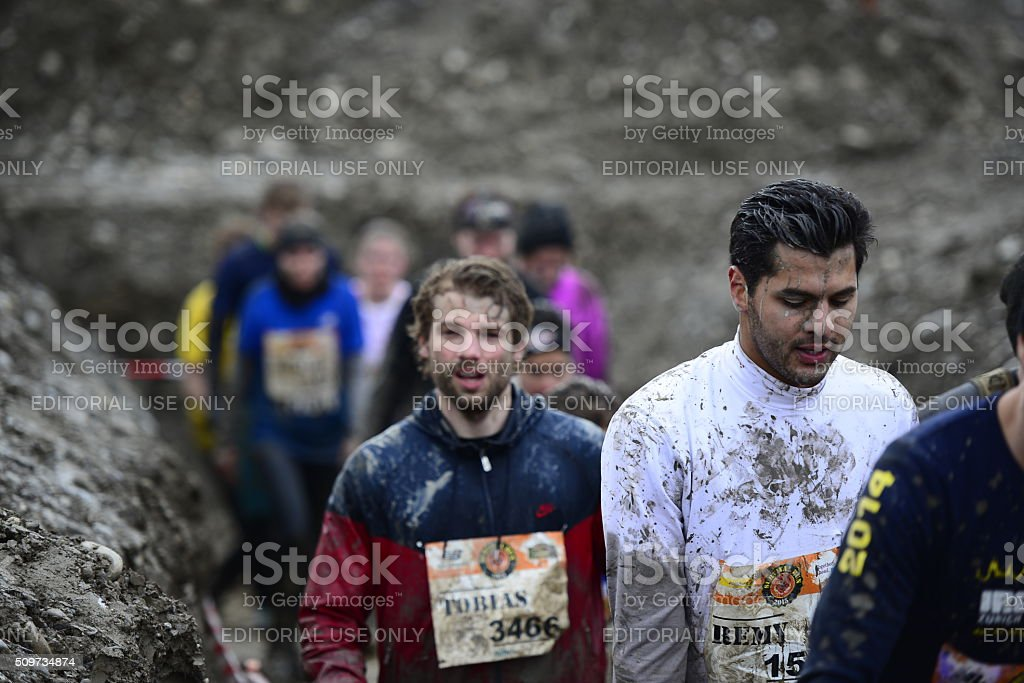 Competitors of the Survival Run Thun run through a ditch that is part...