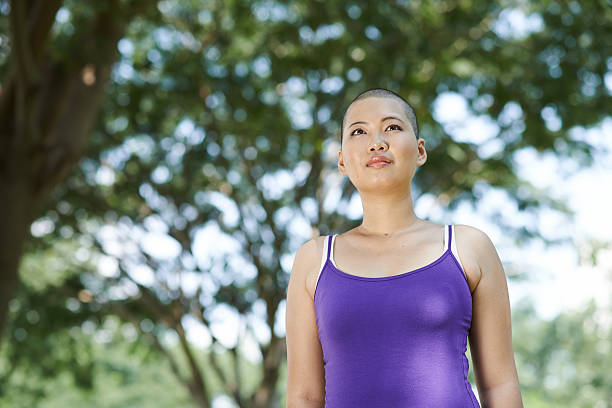 Surviving breast cancer Portrait of woman exercising in park after surviving breast cancer shaved head stock pictures, royalty-free photos & images