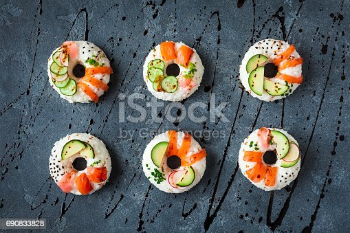 istock Sushi donuts set on black background. Flat lay, top view 690833828