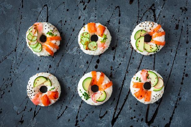 sushi-donuts auf schwarzem hintergrund gesetzt. flach legen, top aussicht - sushi essen stock-fotos und bilder