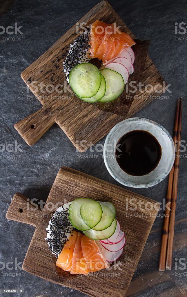 Sushi donuts set with salmon, vegetarian with soy sauce. Sushi trend. Creative food. Dark background. stock photo