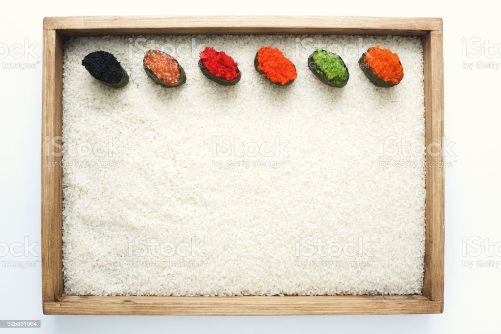 Top view on sushi gunkan with colored caviar in wooden frame on white...