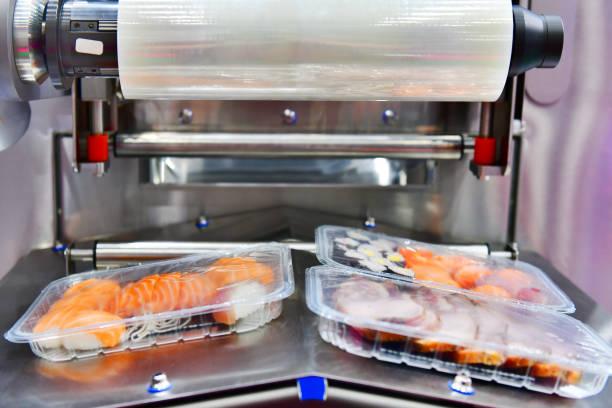 sushi in boxen transfer auf automatisierten fördersystemen für verpackung. - nahrungsmittelfabrik stock-fotos und bilder