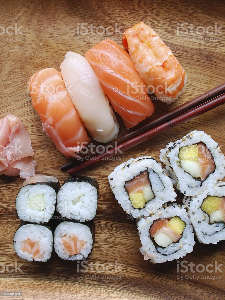 Sushi - Japonese food (on a wooden plate) royalty-free stock photo