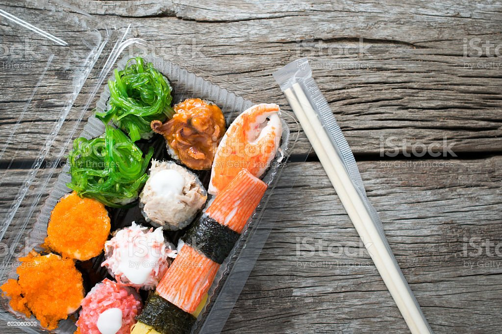 Sushi packs from supermarket on wood table background.