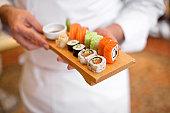 sushi chef holding sushi plate.