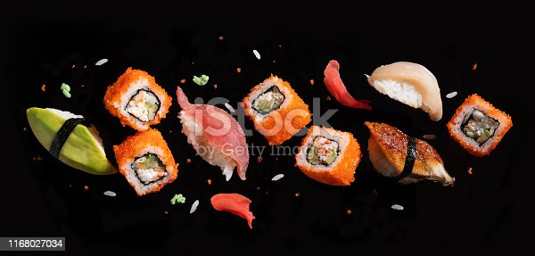 istock Sushi pieces between chopsticks, flying separated on black background. 1168027034