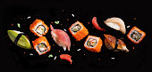 Sushi pieces between chopsticks, flying separated on black background.