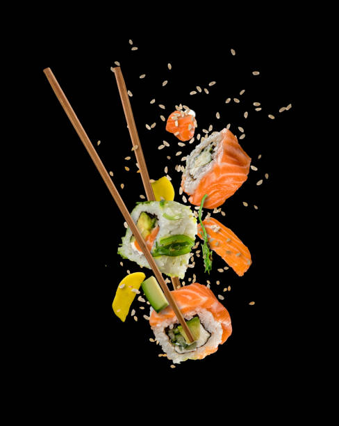sushi pieces placed between chopsticks on black background - sushi stock photos and pictures