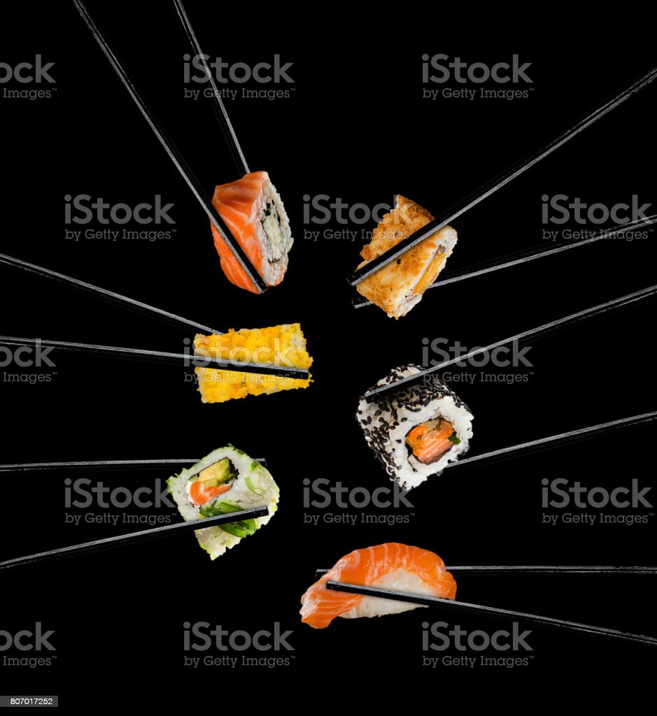 Sushi pieces placed between chopsticks, on black background stock photo