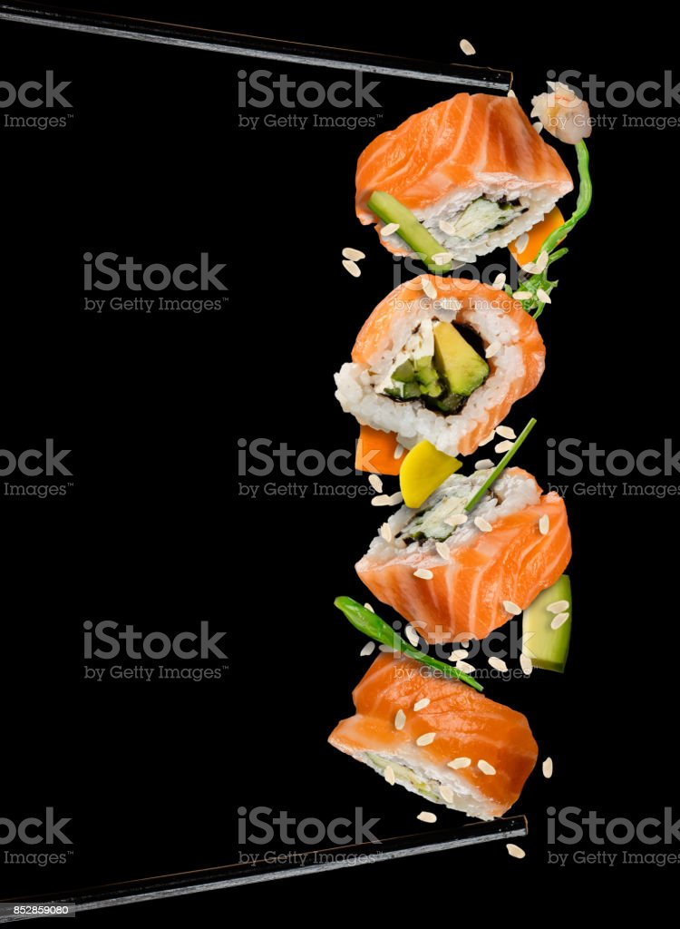 Sushi pieces placed between chopsticks on black background stock photo
