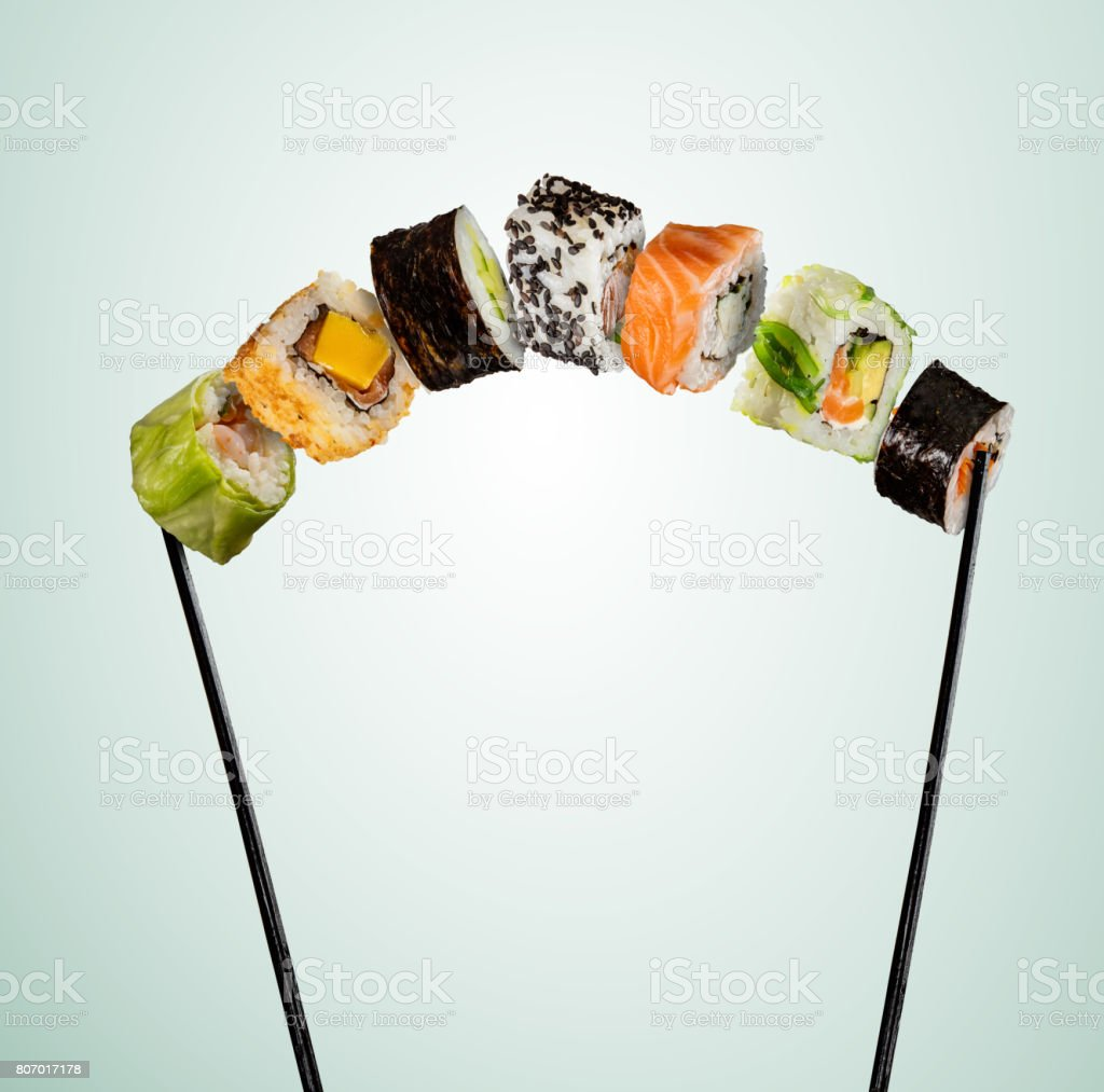 Sushi pieces placed between chopsticks on soft background stock photo