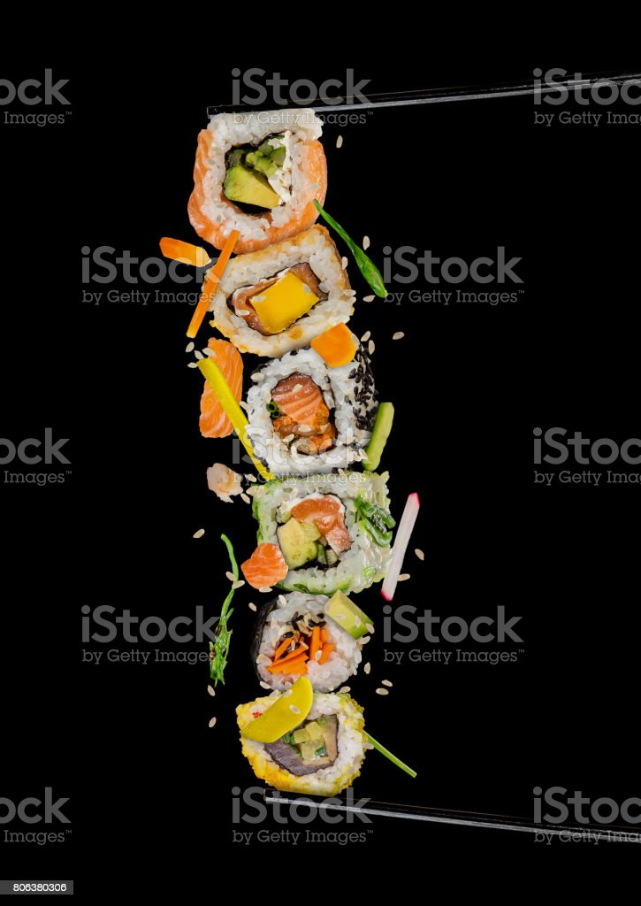 Sushi pieces placed between chopsticks on white background stock photo