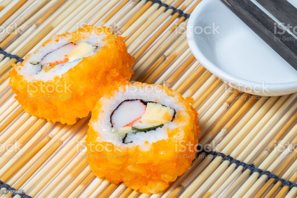 Sushi Roll And Chopstick On Bamboo Rolling Mat Stock Photo