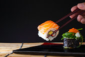 Sushi roll and salmon with chopsticks. Sushi roll japanese food in restaurant,Salmon sushi nigiri in chopsticks over black background.
