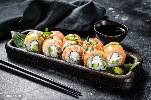 Sushi roll Philadelphia with salmon, avocado, cream cheese. Sushi menu. Japanese food. Black background. Top view.