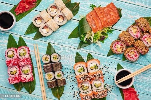 istock sushi roll set . sushi, sashimi, maki flat lay at blue wooden backdrop. japan cuisine. 1147991137