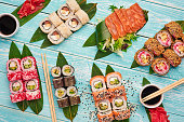 sushi roll set served with bamboo leaves. sushi, sashimi, maki flat lay at blue wooden backdrop. japan cuisine