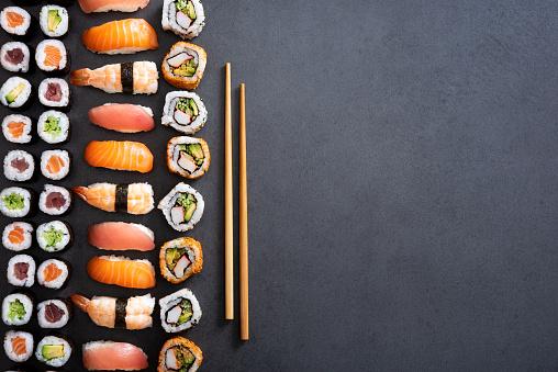 Top view of nigiri, hosomaki, uramaki and wooden chopsticks on black stone. High angle view of sushi rolls and maki on dark blackboard. Japanese food on dark background with copy space.