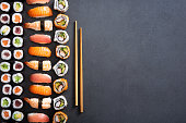 Top view of nigiri, hosomaki, uramaki and wooden chopsticks on black stone. High angle view of sushi rolls and maki on dark blackboard. Japanese food on dark background with copy space.