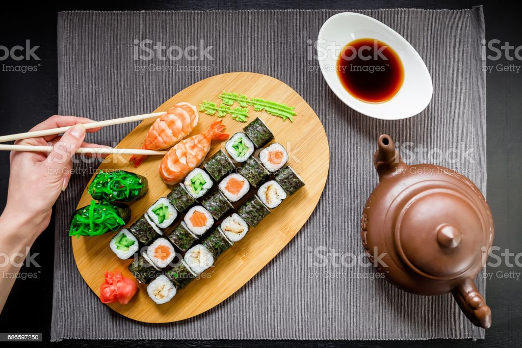 Sushi rolls, sauce and woman hand holding chopsticks on a grey background. Top view. Flat lay. royalty-free stock photo