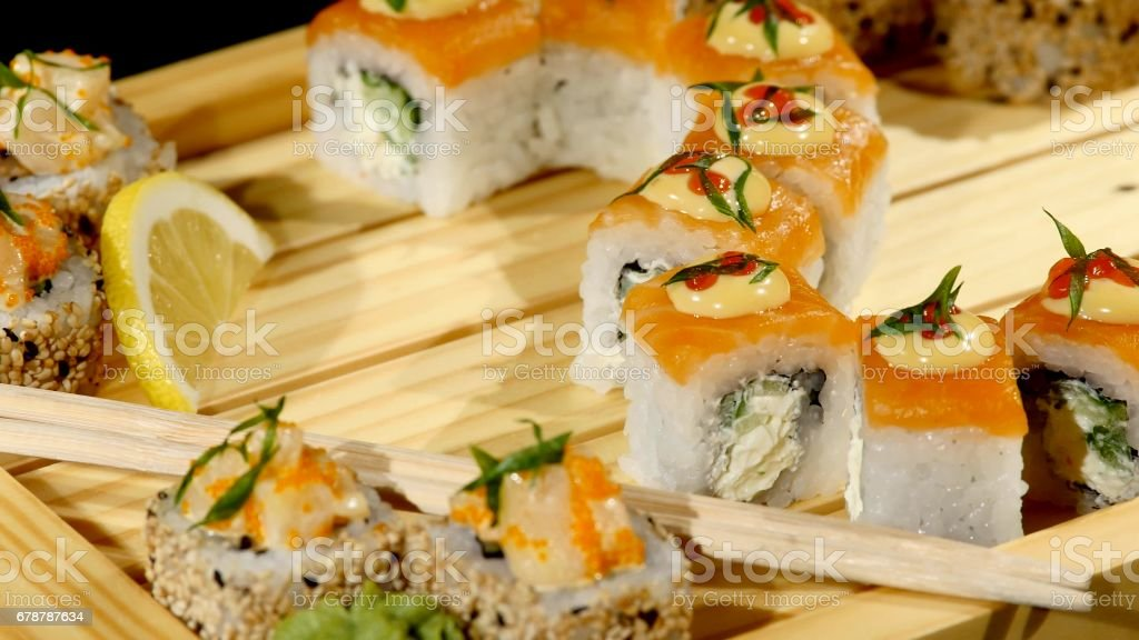 Sushi rolls set on a wooden board close up. rotating on black backround royalty-free stock photo
